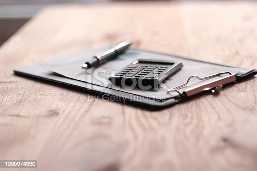 istock close up. blurred image of pen and calculator on desktop 1005974990