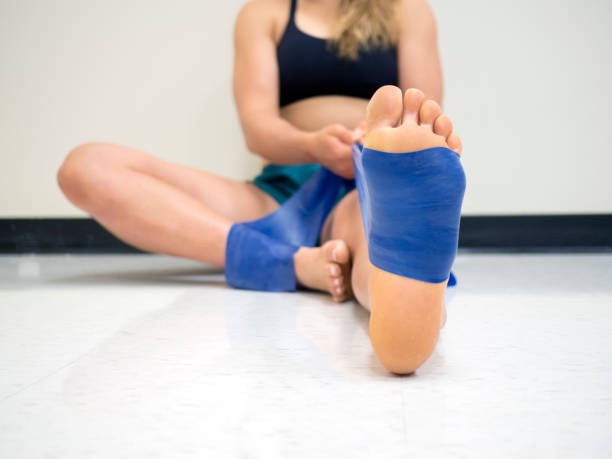 Close up bottom view of an young female athlete using a theraband resistance band on her foot and ankle stock photo
