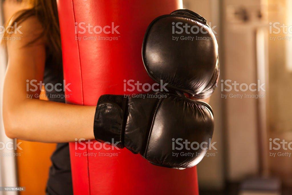 7dde59da3 close-up Boxer mulher abraço saco de boxe com luvas de boxe em aptidão gym