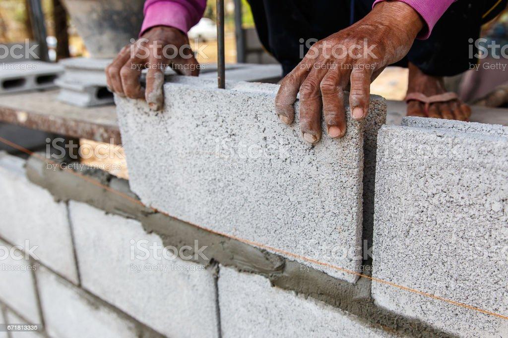 Close up bricklayer worker installing brick masonry on construction site stock photo