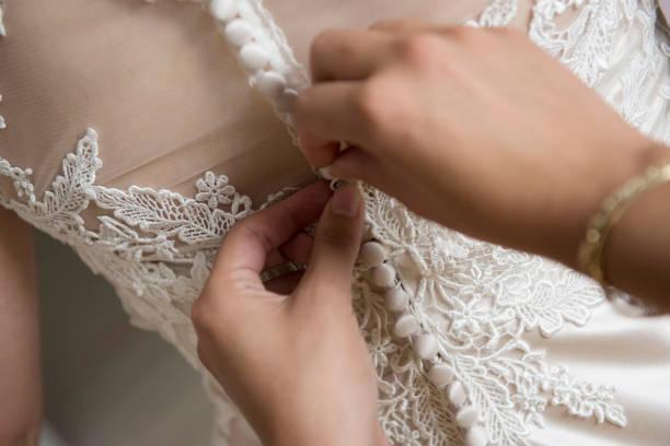 hautnah. brautjungfer ist ein weißes hochzeitskleid schnürung. - hochzeitskleid in schwarz stock-fotos und bilder