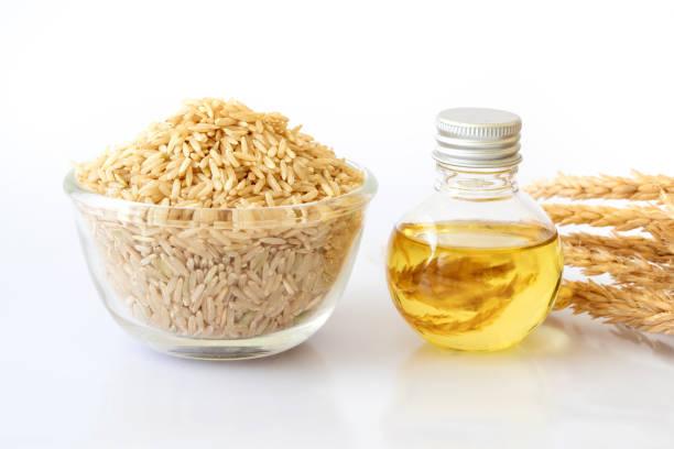 Nahaufnahme der braunen Samen und Reis Reiskleieöl in Flasche und unmilled Reis auf weißem Hintergrund, eine gute Fette für eine gesunde Ernährung – Foto