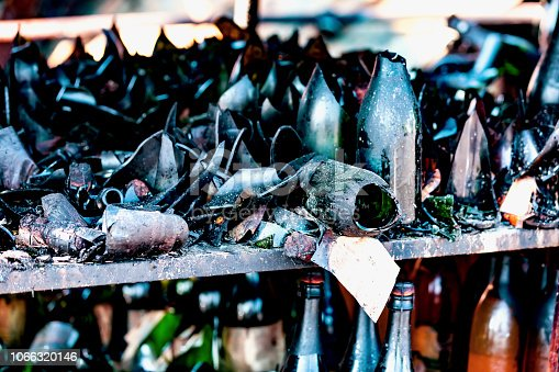Close up damaged supermarket glass plastic bottles after arson fire with burn black dark debris after intense burning fire disaster ruins waiting for investigation for insurance. Saturated contrasting effect dramatic atmosphere