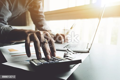 897852992istockphoto close up, business man or lawyer accountant working on accounts using a calculator and laptop computer in his office 896613212