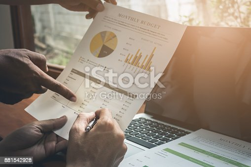 881542122istockphoto Close up Business man pen pointing stock maket with partner work 881542928
