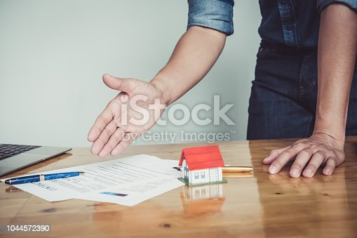 863128060 istock photo Close up business man reaching out sheet with contract agreement proposing to sign.Insurance agent and insurance company customers.Concept of insurance with house and car 1044572390