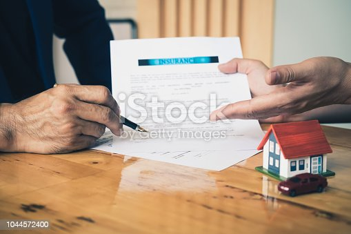 863128060 istock photo Close up business man reaching out sheet with contract agreement proposing to sign.Insurance agent and insurance company customers.Concept of insurance with house and car 1044572400
