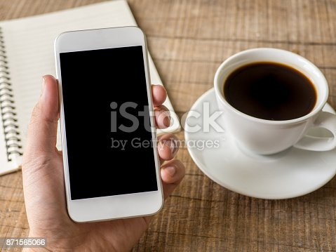 istock Close up business man's hand holds smart phone with black isolated screen over background of notebook, coffee on wooden background 871565066