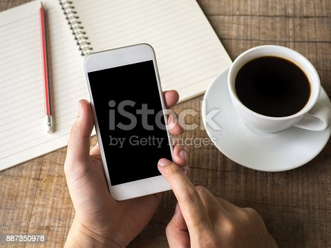 istock Close up business man's hand holds smart phone with black isolated screen over background of notebook, coffee on wooden background 887350978