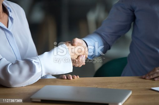 Businesspeople accomplish negotiations with handshake, cropped image hands close up. Business lady greeting businessman people solving important business issues starting successful cooperation concept