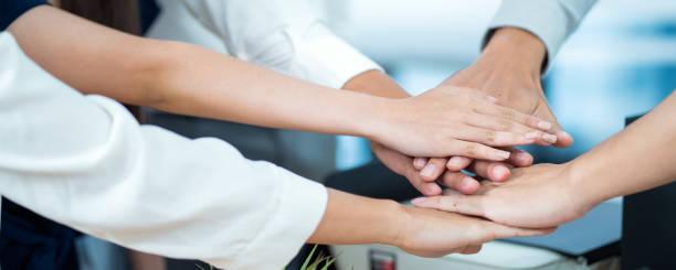 Cerrar el equipo de negocios poniendo sus manos juntas.banner horizontal para el diseño del sitio web - foto de stock