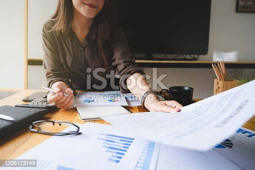 875087884 istock photo Close up Business woman hand holding pen and financial paperwork with financial network diagram. vintage concept. 1205173149