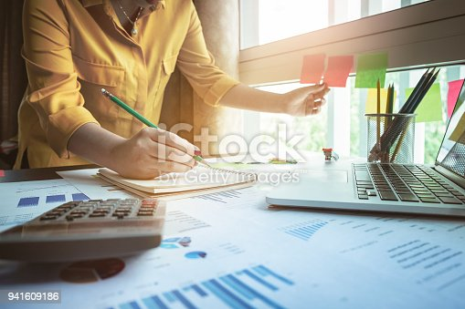 istock Close up Business woman hand holding pencil and touch at post it with financial paperwork. 941609186