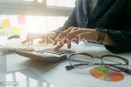istock Close up Business woman using calculator and laptop for do math finance on wooden desk in office and business working background, tax, accounting, statistics and analytic research concept - Image 1085983682