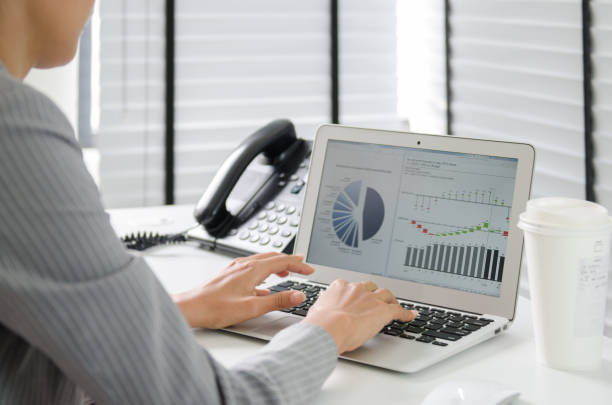 Close up business woman working in office with business graph on computer stock photo