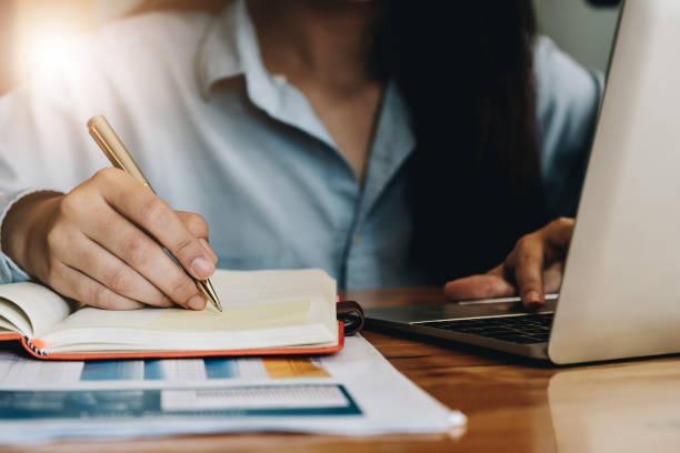 Schließen Sie Business-Frau, die mit Laptop-Computer arbeitet und schreiben Sie auf einem Notizblock mit einem Stift im Büro. Business Financial Concept – Foto