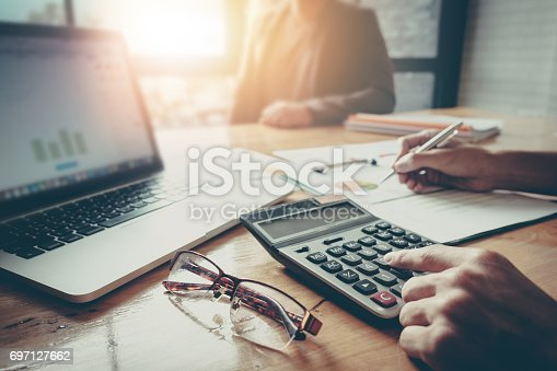 istock Close up Businessman and partner using calculator and laptop for calaulating finance, tax, accounting, statistics and analytic research concept 697127662