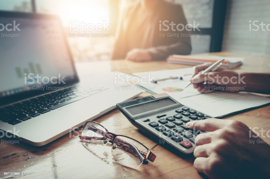 Close up Businessman and partner using calculator and laptop for calaulating finance, tax, accounting, statistics and analytic research concept – zdjęcie