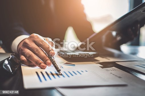 istock Close up Businessman consultant holding pen and pointing at financial on wooden desk in coffee shop. freelance, tax, accounting, statistics and analytic research concept. 956243148