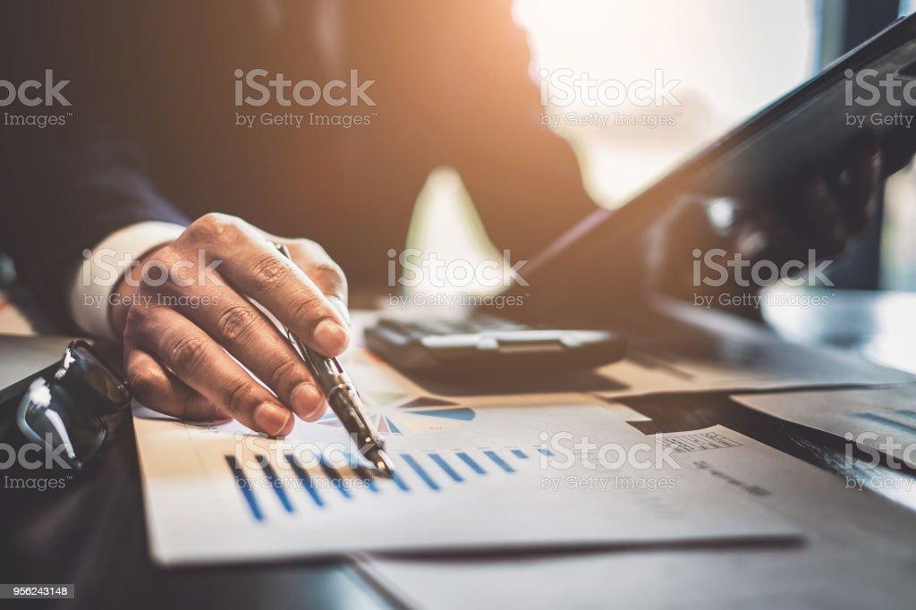 Großaufnahme Geschäftsmann Berater halten Sie Stift und deutete auf finanzielle auf hölzernen Schreibtisch im Coffee-Shop. Freelance, Steuern, Buchhaltung, Statistiken und analytische Forschungskonzept. – Foto