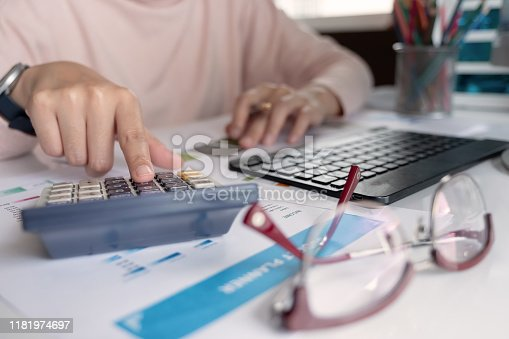 897852992istockphoto Close up Businessman hand holding pen and pointing at finance paperwork and using calculator for do math on wooden desk at office. 1181974697