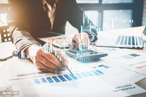 897852992istockphoto Close up Businessman hand holding pen and pointing at finance paperwork and using calculator for do math on wooden desk at office. business finance concept. 897852992