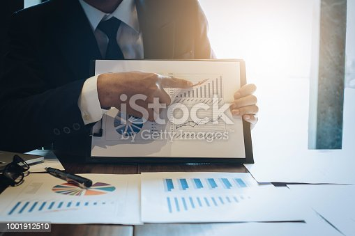 istock Close up Businessman hand holding pen and pointing at financial paperwork. 1001912510
