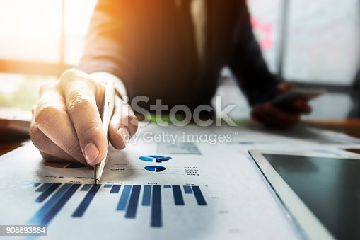 istock Close up Businessman hand holding pen and pointing at financial paperwork. 908893864