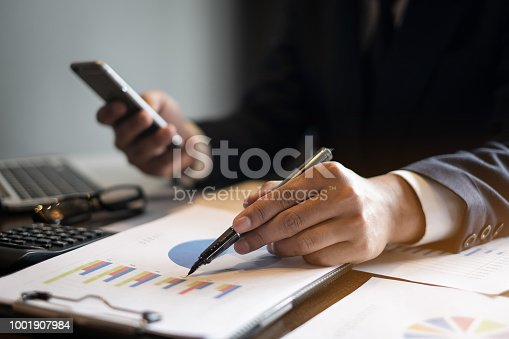 istock Close up Businessman hand holding pen and pointing at financial paperwork with cell phone. 1001907984
