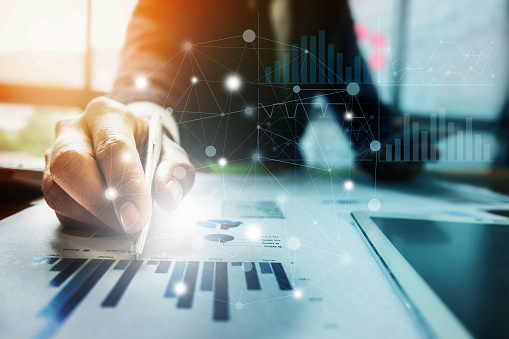 istock Close up Businessman hand holding pen and pointing at financial paperwork with financial network diagram. 875087884
