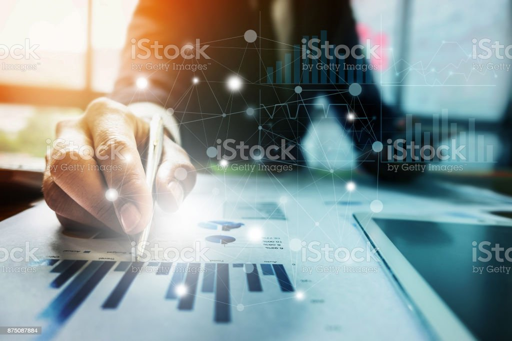 Close up Businessman hand holding pen and pointing at financial paperwork with financial network diagram. stock photo