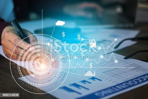 istock Close up Businessman hand holding pen and pointing at financial paperwork with financial network diagram. 956243636
