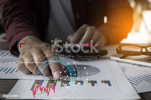 istock Close up Businessman hand holding pen and pointing at financial paperwork with financial network diagram. 956243662