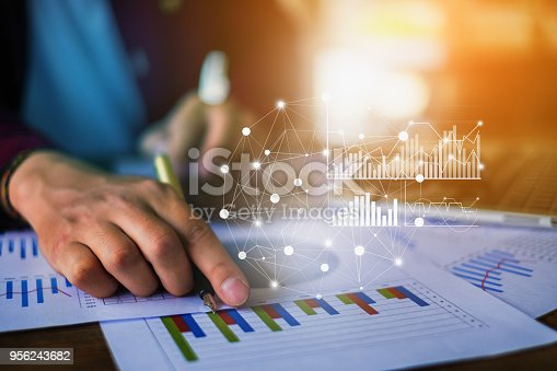 istock Close up Businessman hand holding pen and pointing at financial paperwork with financial network diagram. 956243682
