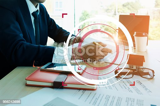istock Close up Businessman hand holding pen and pointing at financial paperwork with financial network diagram. 956243698