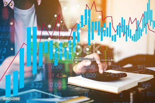 istock Close up Businessman hand holding pen and using calculator for do math with financial network diagram. business financial concept. 956243588