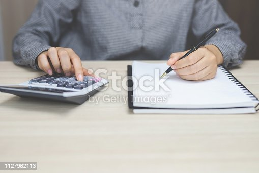 istock Close up businessman hand using calculator and writing in a notebook counting making notes Accounting at doing finance at home office. Savings finances concept. note pad 1127982113