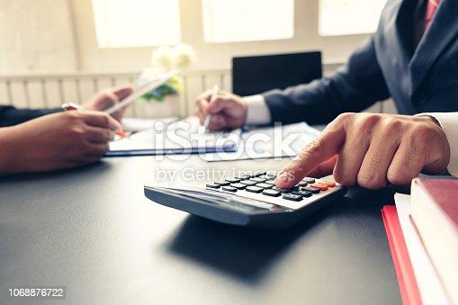 1068752548 istock photo Close up businessman hand using calculator at meeting. 1068876722