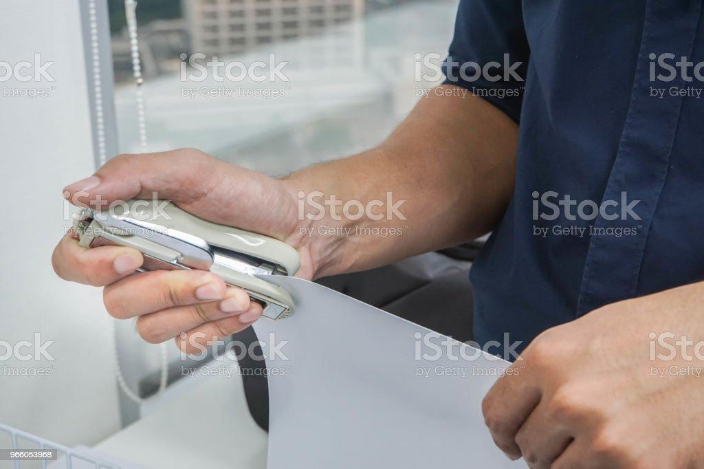 Stäng upp affärsman hand med häftapparat för dokument i ordning i office - Royaltyfri Arbeta Bildbanksbilder