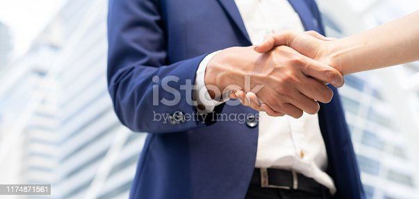 istock close up businessman handshake with businesswoman at outside city building background after completed conference meeting event about company's profit in the future concept 1174871561