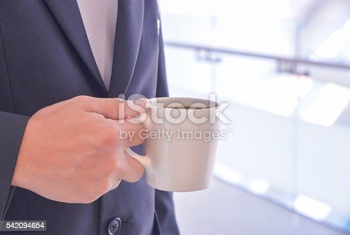 istock Close up businessman holding a cup of coffee. 542094654