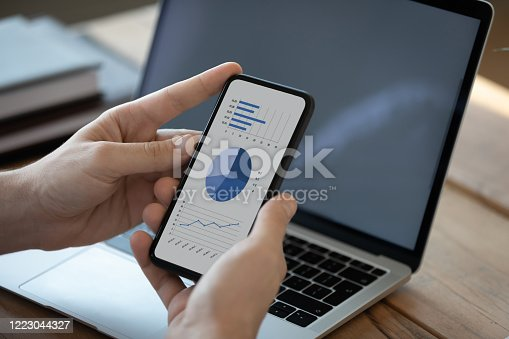 872006502 istock photo Close up businessman holding phone with diagrams on screen 1223044327