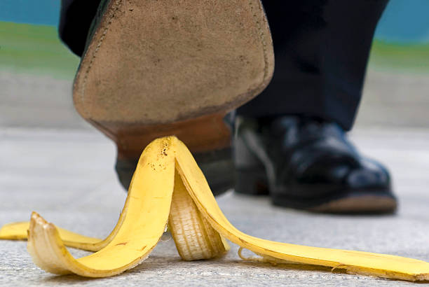 Close up businessman stepping on banana skin Close up businessman stepping on banana skin banana peel stock pictures, royalty-free photos & images