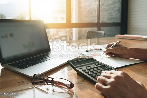 istock Close up Businessman using calculator and laptop for calaulating finance, tax, accounting, statistics and analytic research concept 697127716