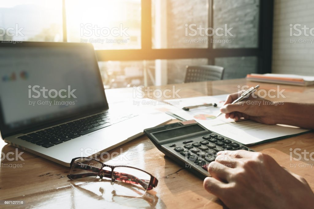 Close up Businessman using calculator and laptop for calaulating finance, tax, accounting, statistics and analytic research concept stock photo