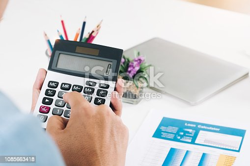 897852992istockphoto Close up Businessman using calculator and laptop for do math finance on wooden desk in office and business working background, tax, accounting, statistics and analytic research concept - Image 1085663418