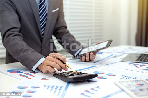 istock Close up businessman using calculator and tablet in the calculations revenue and market statistics. 1044944124