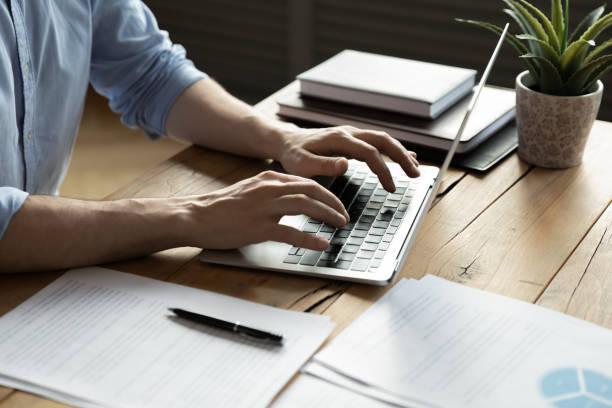 ラップトップを使用してビジネスマンを閉じ、ワークデスクに座る - パソコン ストックフォトと画像