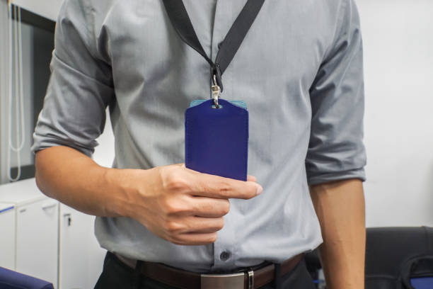 close up businessman with grey shirt hold neck company badge in office - badge stock pictures, royalty-free photos & images