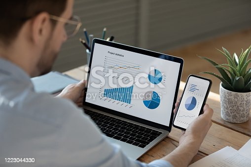 872006502 istock photo Close up businessman working with statistics on laptop and phone 1223044330